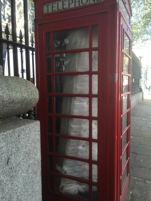red phone box with a mattress inside