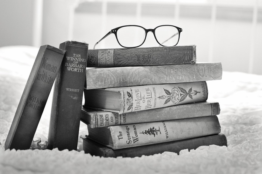 black and white image of a pile of books demonstrating different genres