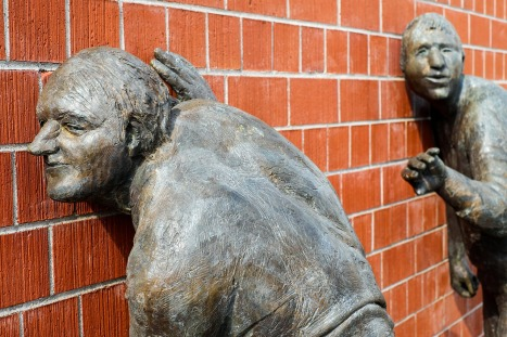 sculptured people with their ears pressed up against a wall listening