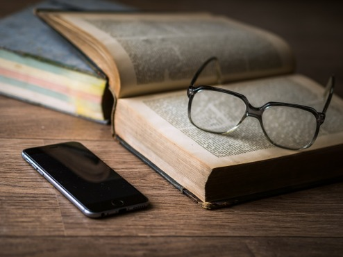 image showing open book, glasses and mobile phone