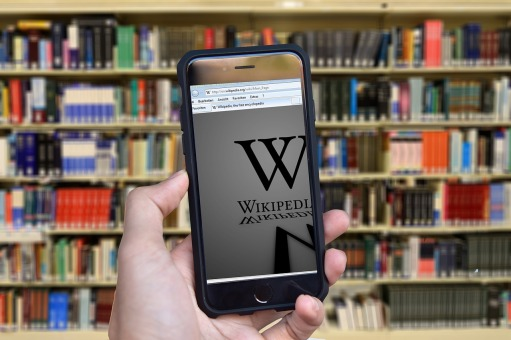 image of bookshelves and a mobile device showing wikipedia