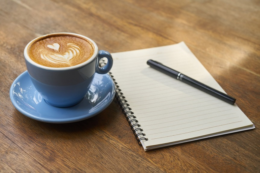 coffee cup, note pad and pen