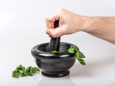 image of herbs being crushed in a bowl