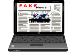 laptop wth screen showing the words Fake News