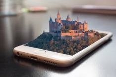 mobil phon with a landscape of trees and a castle emerging from the screen