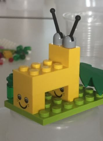 yellow lego snail with smile on bricks