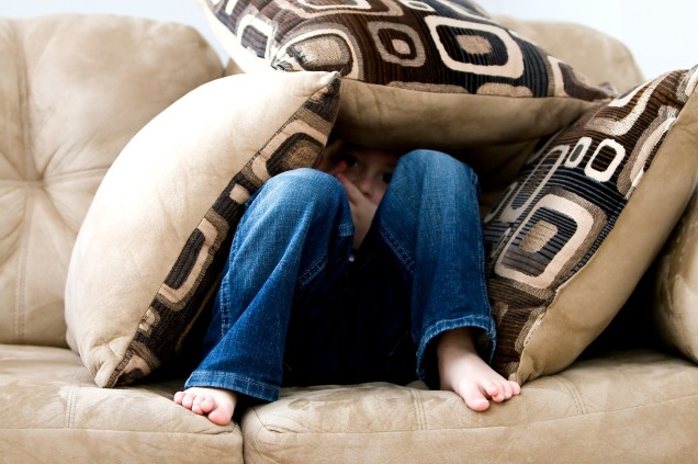 person hiding underneath cushions