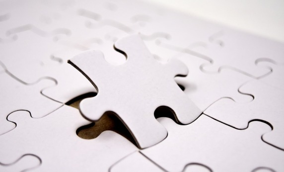 image showing a jigsaw where all the peices are white and one is being taken out