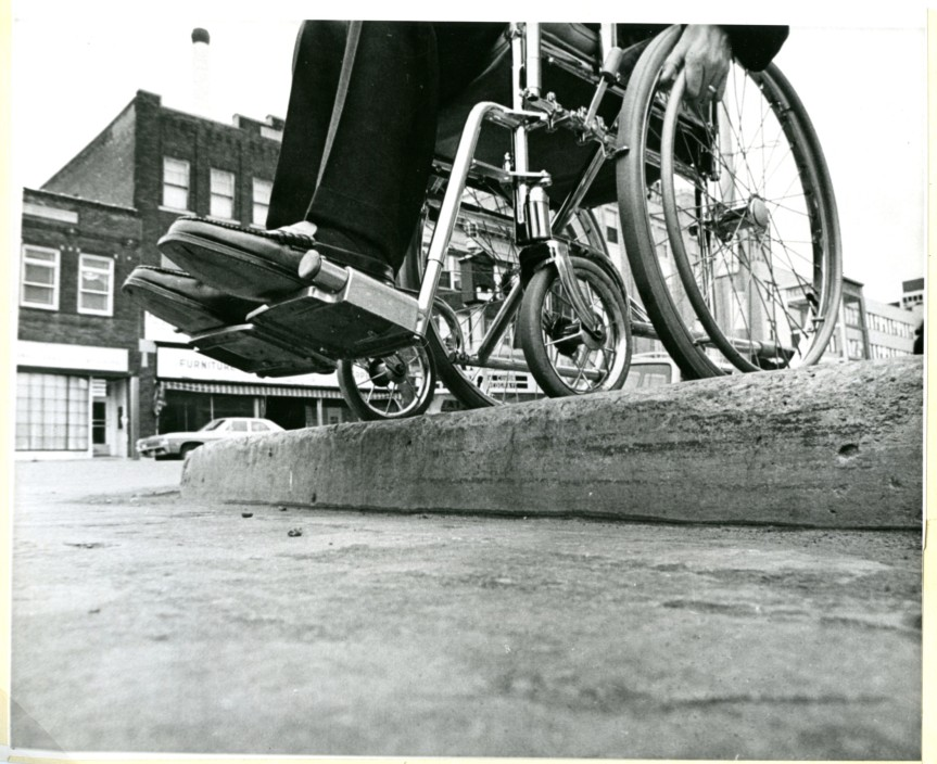 black and white image of a wheelchair on the edge of a kerb