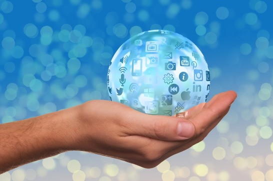 image shpowing a hand holding a blue ball covered with social media icons