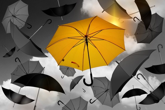 image showing black open umbrellas surrounding a central yellow one