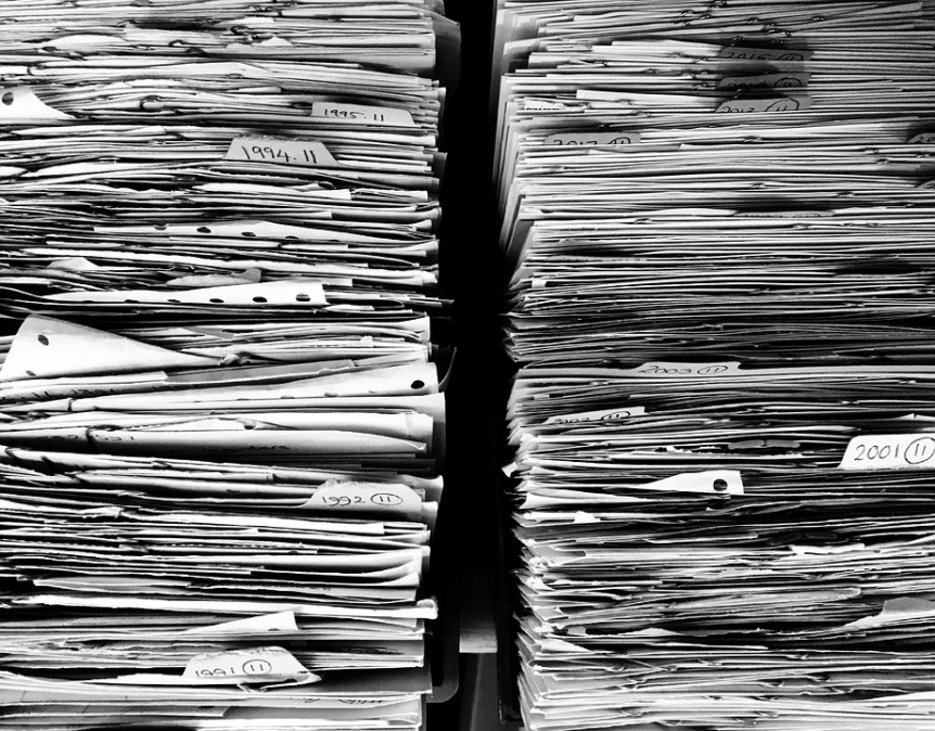 black and white image showing piles of paper files and documents